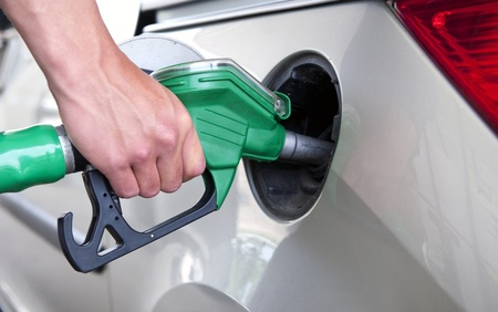 Hand, refuelling a passenger car, holding a green fuel pump photo