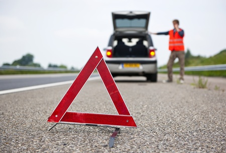 car trunk: Warning tiangle behind a broken down car with a motorist calling for assistance. Focus on the triangle Stock Photo
