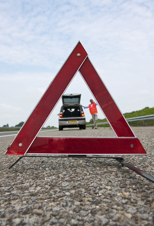Warning triangle, with a broken down car and a man calling for assistance, out of focus in the backgrond photo