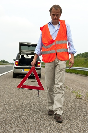 Man walking backwards from his car wearing a safety vest, carying a warning triangle photo