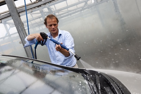 car wash: Man washing the windscreen of his car in a cubicle with a high pressure water jet