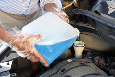 refilling: Man wearing plastic gloves, refilling windscreen wiper fluid in his car