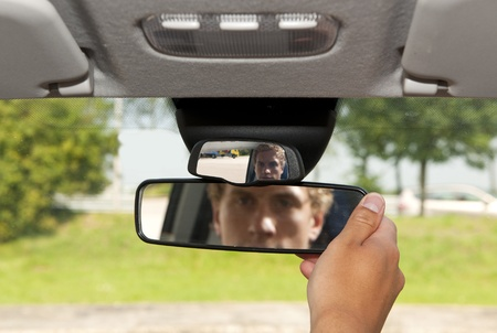 windscreen: Man, adjusting the rear view mirror of his car