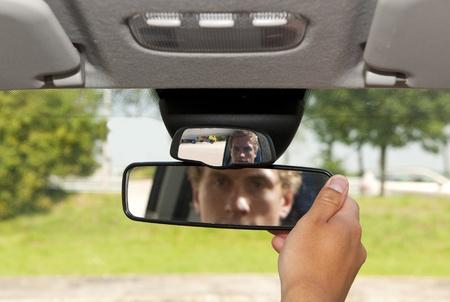 adjust: Man, adjusting the rear view mirror of his car