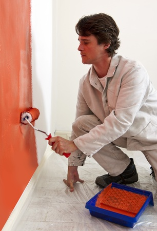 Painter, painting a wall orange with a paint roller photo
