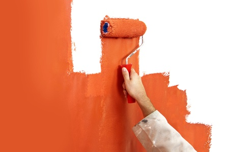bisected: Hand with paint roller covered in bright orange, painting over a white wall