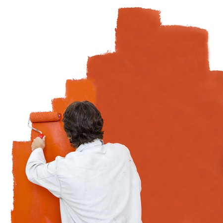 Painter using a paint roller to paint a wall orange photo