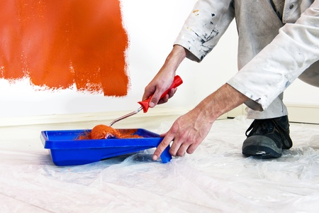 painters: Painter refilling his paint roller whilst painting the walls in a room