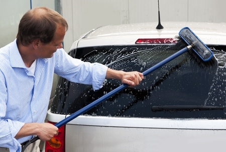 tinted: Man washing the rear window of his car with a broom, soap and water Stock Photo
