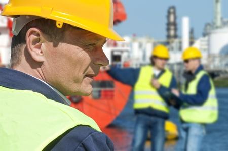 trabajador petroleros: Retrato de un docker delante de una escena de puerto con dos de sus compañeros de trabajo fuera de foco en segundo plano