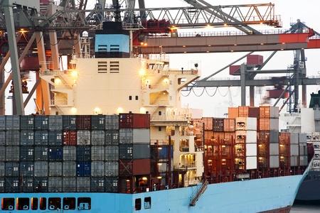 containerschip: Een grote containerschip wordt gelost in de vroege ochtend in een industriële haven van bovenloopkranen Stockfoto