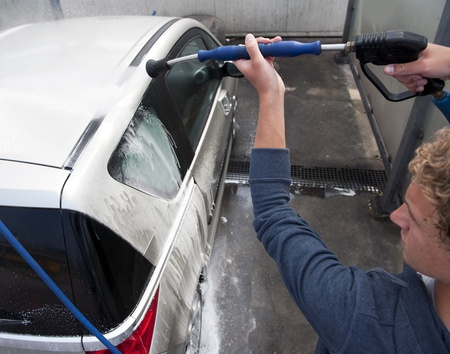 washing car: Water spray gun, held by a man, used to wash a car with soap