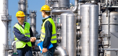 oil industry: Two petrochemical contractors closing a deal in front of an oil refinary Stock Photo