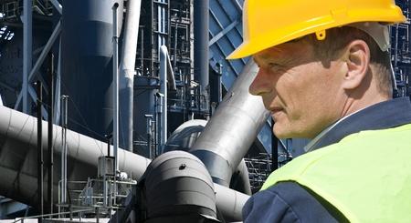 retardant: Stern lavoratore guardando davanti a una fabbrica imponente di un impianto dell'industria pesante