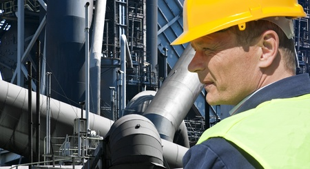 blue collar: Stern looking worker in front of an imposing factory of a heavy industry facility Stock Photo