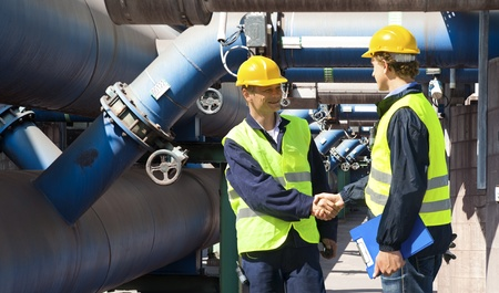 Two engineers meeting outside at the piping of an industrial waste water cleaning facility Stock Photo