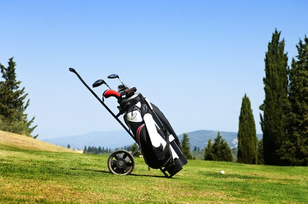 Golf bag with several clubs on a trolley on the fairway of a golf course Stock Photo