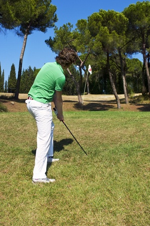 Golf player chipping his ball on the green of a luxurious golf course photo