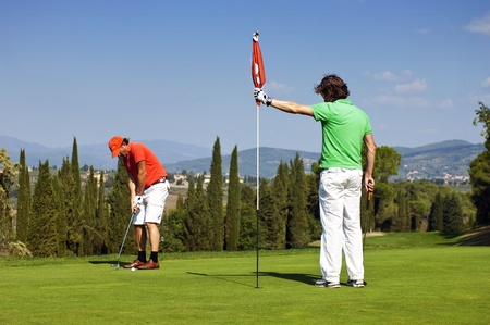 opponents: Flight of two golfers playing on the green of a golf course