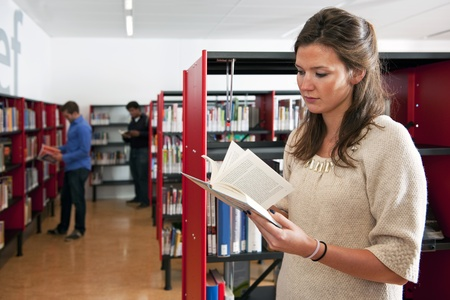 Young woman thumbing through a book in a library, with two other visitors in the background Stock Photo - 11293720