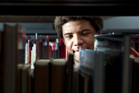 Young man browsing through the racks of books in a library photo