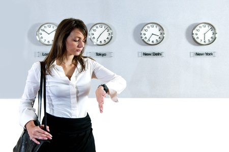 impatient: Young business woman checking the time on her watch with various international clocks, displaying world time, in the background