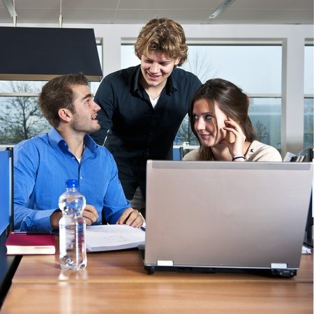 Three students working together on a project in a library Stock Photo - 11293718
