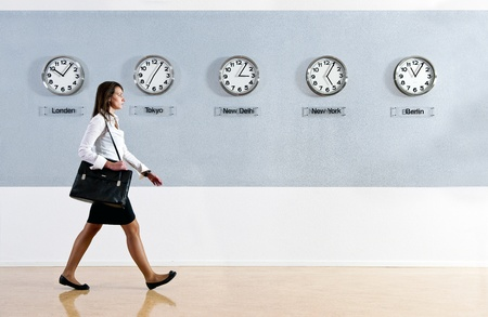 world of work: Business woman walking hurrily past a row of clocks showing the time in various parts of the world. Business, travel, time concept Stock Photo