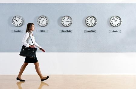 mujer sola: Mujer de negocios caminando hurrily pasado una fila de relojes que muestran el tiempo en diversas partes del mundo. De negocios, viajes, concepto de tiempo