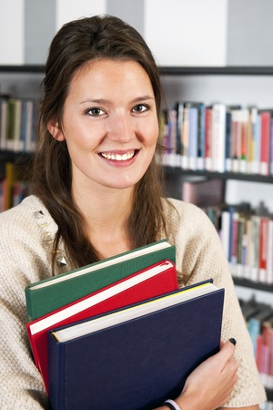 Smiling young woman holding a stack of colorful hardcover books in a library photo