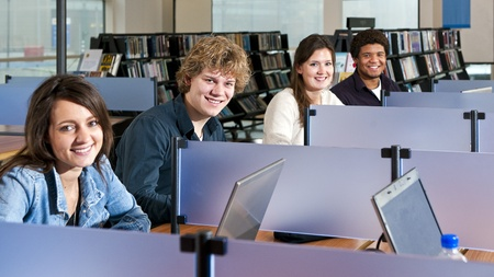 Four students studying in cubicles in a public library, with focus on the second young adult man Stock Photo - 11293712