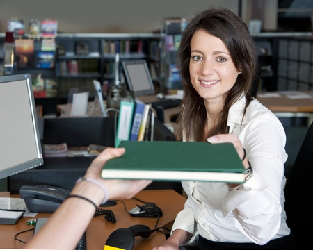 woman hard working: Young smiling female librarian handing a book to a customer