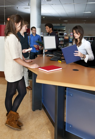 A queue of customers waiting at the check out desk, where a librarian is scanning books photo