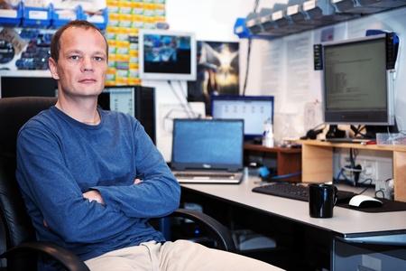 Porträt eines streng dreinblickende EDV-Techniker in einem unordentlichen Werkstatt, mit verschiedenen Computern, Bildschirmen und Hardware-Komponenten im Hintergrund