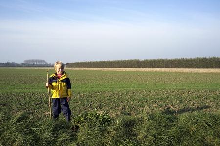 botas de lluvia: Niño pequeño con un palo, el desgaste lleva la lluvia en el campo plano, frente a un campo de la recién sembrada de trigo