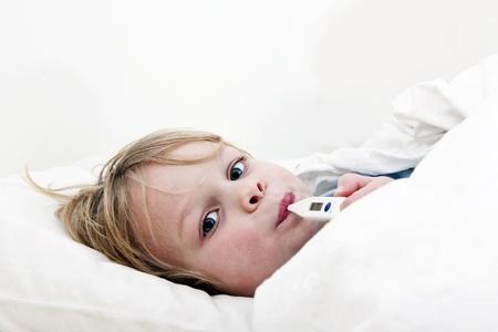 fiebre: Ni�o peque�o enfermo, acostado en la cama con un thermomether, midiendo la altura de la fiebre y mirando a la c�mara Foto de archivo