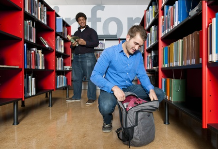 shelfs: Man, kneeling to get something out of his back pack in a public library in between the shelfs, with another man out of focus in the background
