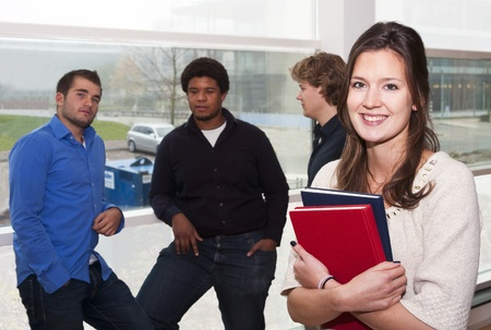 Portrait of a young, female, student, holding a couple of books with a group of guys leaning in the window still in the background Stock Photo - 11864347