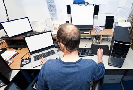 geek: El hombre detrás de un escritorio con varios ordenadores y pantallas, reparación e instalación de nuevo hardware