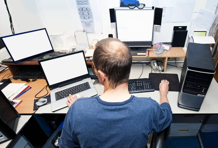 computer hacker: Man behind a desk with several computers and screens, repairing and installing new hardware