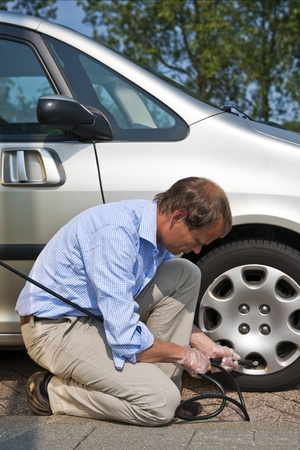 kneeling man: Man, kneeling at the curb, and inflating the front tyre of his car using an automated air pressure hose