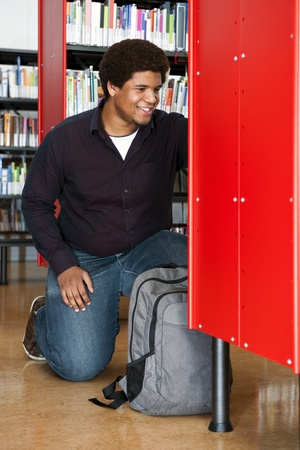 African man, kneeling in between the bookshelves in a public library, smiling, with a backpack in front of him Stock Photo - 11864396