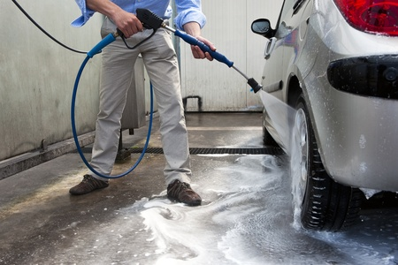 hoses: Man, wahsing his car in the stall of a car wash, using a high pressure water jet