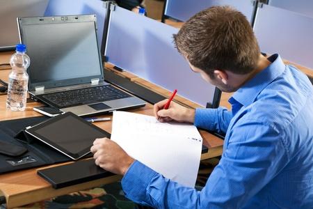 Student Notizen auf seinem Notizblock, sitzt hinter einem Schreibtisch mit einem Laptop und andere elektronische Geräte Standard-Bild