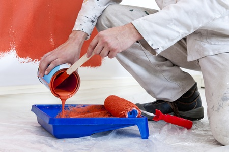 decorator: Painter, reffiling a tray with orange wall paint