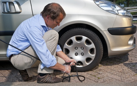inflating: Kneeling man, inflating the right front tyre of his car at a gas station Stock Photo