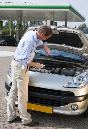 motor oil: Man, checking the oil level of the engine of his car at a gas station Stock Photo
