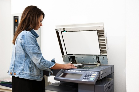 photocopier: Woman copying notes on a coin operated photocopier