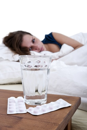 Sick woman in bed, looking at a glass of water, and two blister strips with pills photo