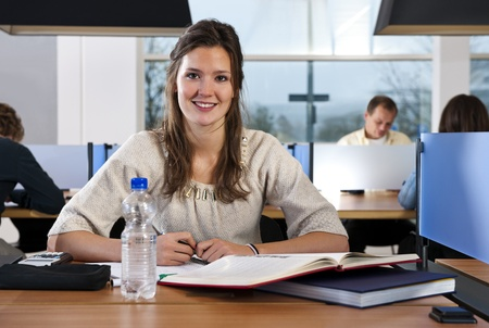 Young, smiling student in a busy library, looking into the camera, with several people in the background Stock Photo - 11864377